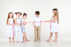 Little girls draw over rope and boy looks at rope. Four little girls in white clothes draw over pink rope and boy looks at rope Royalty Free Stock Photo