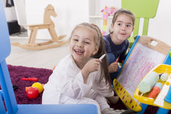 Little girls draw in the room Stock Photography