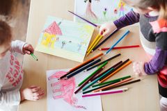 Little girls drawing a colorful pictures of elephant and playing. Children using pencil crayons standing at table indoors. Shot from above Stock Images