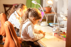 Little girls drawing pictures behind desk Royalty Free Stock Image