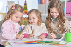 Little girls drawing. Three cute little girls drawing with pencils Stock Image