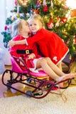 Little girls dressed as Santa near Christmas tree Royalty Free Stock Image
