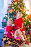 Little girls dressed as Santa near Christmas tree Royalty Free Stock Photo