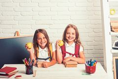 Little girls eat apple at lunch break. Friendship of small sisters in classroom at knowledge day. School time of girls. Happy school kids at lesson in stock photography