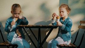 Little girls eat ice cream in front of the restaurant. Two little girls eat ice cream in front of the restaurant in summer stock video
