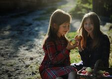 Little girls eating apples near the tree in the village