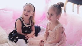 Little girls eating birthday liquorice. Two little girls on a children`s birthday. Embrace and have fun stock footage