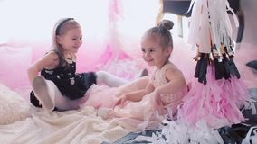Little girls eating birthday liquorice. Two little girls on a children`s birthday. Embrace and have fun stock video