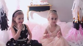 Little girls eating birthday liquorice. Two little girls on a children`s birthday. Embrace and have fun stock video footage