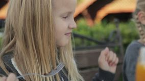 Little girls eating delicious desserts at the cafe stock footage
