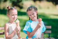 Little girls eating ice-cream outdoors at summer in outdoor cafe stock image