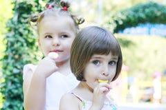 Little girls eating lollipops Royalty Free Stock Images