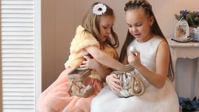 Little girls in elegant dresses consider gifts for the holiday, play and have fun. Beautiful little girls with gifts in home interior stock footage