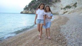 Little girls having fun at tropical beach during summer vacation. Little girls enjoy summer vacation on the beach stock footage