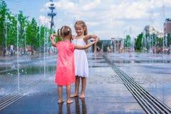 Little girls enjoy sunny day in open street Stock Photos