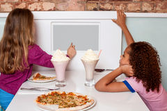 Little girls enjoying pizza in a restaurant. Little girls ordering pizza online in restaurant Stock Images