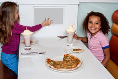 Little girls enjoying pizza in a restaurant Stock Image