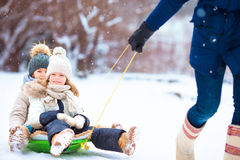 Little girls enjoying sledding. Father sledding his little adorable daughters. Family vacation on Christmas eve outdoors Royalty Free Stock Photo