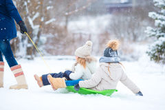 Little girls enjoying sledding in winter day. Father sledding his little adorable daughters. Family vacation on Royalty Free Stock Photo