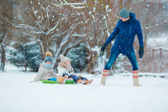 Little girls enjoying sledding in winter day. Father sledding his little adorable daughters. Family vacation on Stock Photos