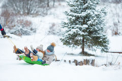 Little girls enjoying sledding in winter day. Father sledding his little adorable daughters. Family vacation on Royalty Free Stock Photos
