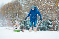 Little girls enjoying sledding in winter day. Father sledding his little adorable daughters. Family vacation on Stock Image