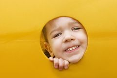 Little girls face through a hole in play equipment. A little girl sticks her face through a hole in a yellow plastic piece of playground equipment royalty free stock photos