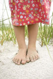 Little Girls Feet in the Sand. Closeup of a little girl's barefoot feet that are covered in sand. Vertical shot Royalty Free Stock Photo