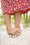 Little Girls Feet in the Sand. Closeup of a little girl's barefoot feet that are crossed and covered in sand. Vertical shot Royalty Free Stock Photos
