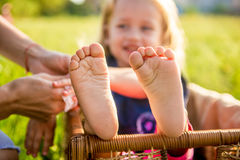 Little girls feet sitting in a wicker basket on a sunny day. In the park Stock Photo
