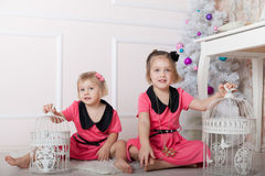 Little girls  on   floor with   bird cages Royalty Free Stock Photography