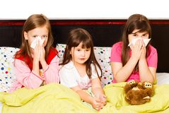 Little Girls With Flu. Sick little girls suffering from bad influenza, staying in bed Stock Photo