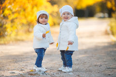 Little girls - girlfriends walk in the park. Stock Images