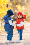 Little girls - girlfriends walk in the park. Royalty Free Stock Images