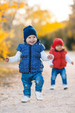 Little girls - girlfriends walk in the park. Stock Photos