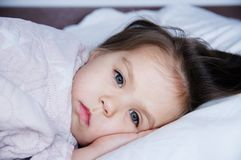 Little girls going to sleep lying on bed. sleep schedule in domestic lifestyle. cute child portrait. Little girls going to sleep lying on bed. sleep schedule in royalty free stock image