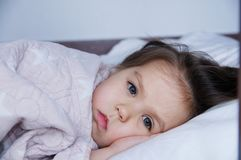 Little girls going to sleep lying on bed. sleep schedule in domestic lifestyle. baby child portrait. Little girls going to sleep lying on bed. sleep schedule in stock image