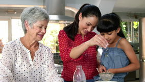 Little girls, grandma and his mom preparing cake stock video