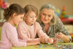 Little girls with grandmother collecting puzzles. Cute little girls with grandmother collecting puzzles together Royalty Free Stock Image