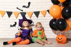Girls in halloween costumes. Little girls in halloween costumes with balloons and pumpkin bucket sitting on the floor stock photos