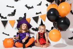 Girls in halloween costumes. Little girls in halloween costumes with balloons and pumpkin bucket sitting on white background stock photography