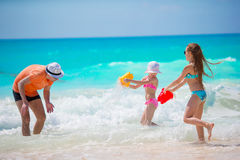 Little girls and happy dad having fun during beach vacation Stock Photos