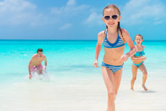 Little girls and happy dad having fun on the seashore. Close-up the youngest daughter running on the beach Stock Image
