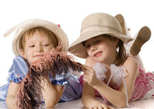 Little girls in hats lie on floor. Beautiful little girls with feather in dresses and in hats lie on the floor, isolated on white royalty free stock image