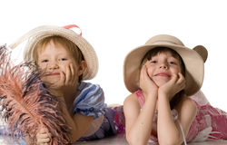 Little girls in hats lie on the floor and smile. Beautiful little girls in hats and dresses lie on the floor, isolated on white royalty free stock images