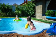 Little girls have fun and swim in the pool Royalty Free Stock Photo