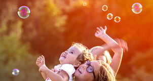 Little girls having bubble fun outdoors Stock Photos