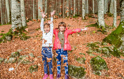 Little girls  having fun with laves in autumn in Biogradska Gora Royalty Free Stock Images