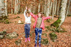 Little girls  having fun with laves in autumn in Biogradska Gora Stock Images