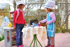 Little girls having fun playing cooking royalty free stock images